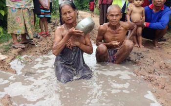 2ตายายอาบน้ำบ่อโคลน ประชดสภาพถนนพัง ทนมา20ปี (ชมคลิป)